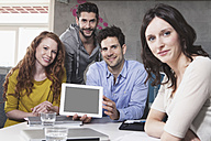 Group picture of four creative people showing tablet computer in the office - RBF001654