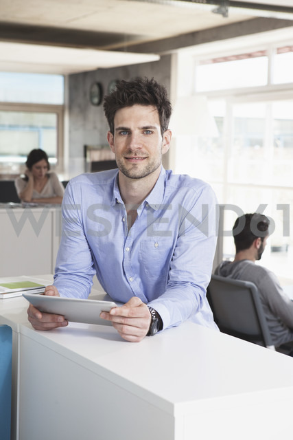 Portrait of smiling man with tablet computer in the office - RBF001685