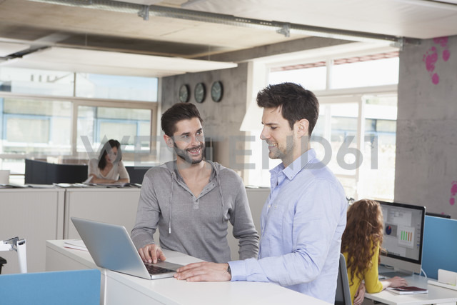 Two colleagues with laptop in an open space office - RBF001663