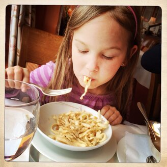 Six year old girl eats spaetzle in a restaurant - DHL000395