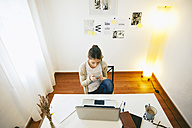 Woman with smartphone at modern home office, elevated view - EBSF000156