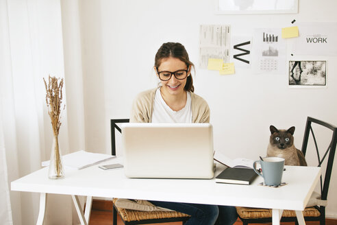 Woman and her cat sitting at desk - EBSF000177