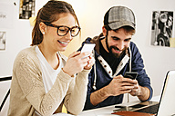 Young couple with smartphones at modern home office - EBSF000159