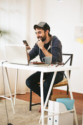 Man with smartphone at modern home office - EBSF000173