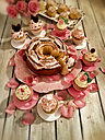 Cup cakes, cup shape, muffins, sponge cakes in shape of a rose, roses, rose petals, gray wooden table, wooden background, studio - CSF021249