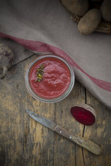 Preserving jar of beetroot potato soup, kitchen knife, cloth and beetroot on dark wood, elevated view - LVF001051