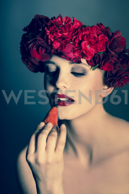 Portrait of young woman wearing red flowers looking at strawberry - FCF000033 - Christina Falkenberg/Westend61