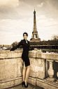 France, Paris, elegant dressed woman posing on bridge in front of Eiffel Tower - FCF000029