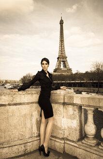 France, Paris, elegant dressed woman posing on bridge in front of Eiffel Tower - FCF000029