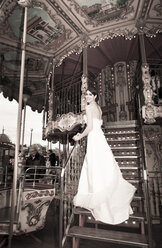 Young woman wearing wedding dress standing on steps of an old carousel - FC000027