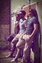 Three young men waiting in front of old industrial building - HOHF000714