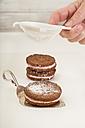 Sprinkling icing sugar on Whoopie pie - CSTF000256