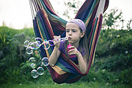 Portrait of little girl blowing soap bubbles - SARF000498