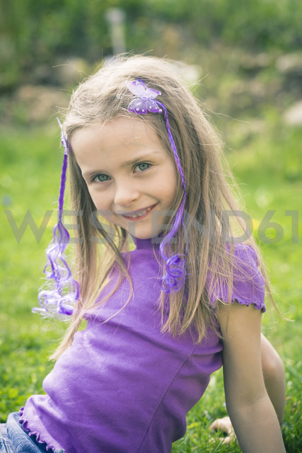 Portrait of smiling little girl sitting in the garden - SARF000496