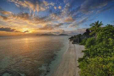 Seychelles, La Digue, view to Anse Source d' Argent with sculpted rocks and palm trees at sunset - RUEF001234