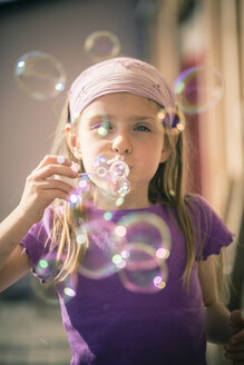 Portrait of little girl blowing soap bubbles - SARF000493