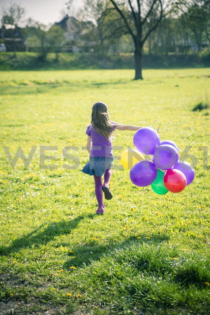 Little girl with balloons running on a meadow - SARF000491