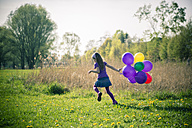 Little girl with balloons running on a meadow - SARF000490