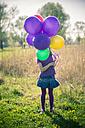 Little girl's face hidden behind balloons - SARF000489