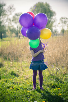 Little girl's face hidden behind balloons - SARF000489