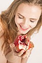 Portrait of smiling young woman eating pomegranate - FCF000039