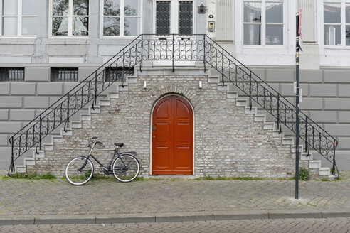 Netherlands, Maastricht, town house with double stairway, bicycle and red door - HLF000457