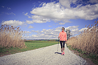 Female Nordic walker on the move through the rural landscape - VTF000214