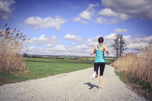 Woman jogging through the rural landscape - VTF000212