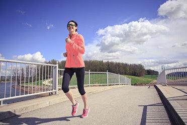 Woman jogging over a bridge - VTF000211