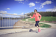 Woman jogging over a bridge - VTF000208