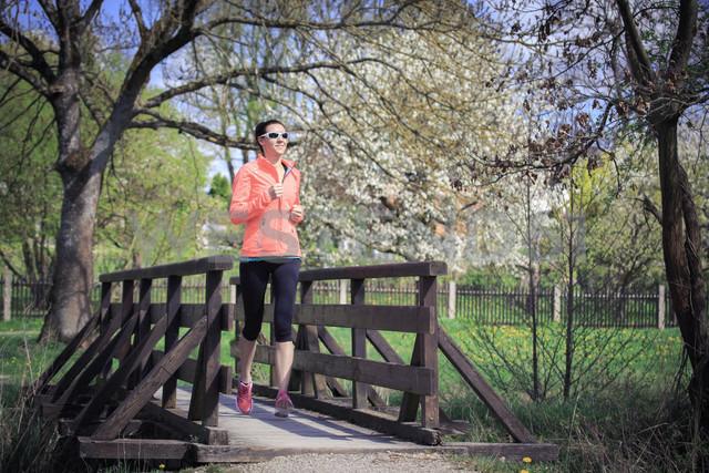 Woman jogging over a footbridge - VTF000205 - Val Thoermer/Westend61