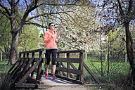 Woman jogging over a footbridge - VTF000205