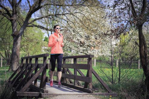 Woman jogging over a footbridge - VTF000205