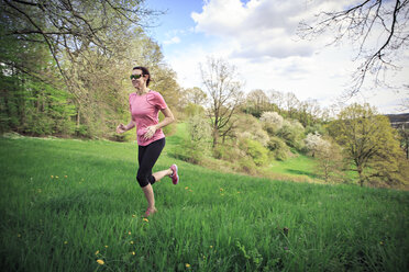 Woman jogging through the rural landscape - VTF000200