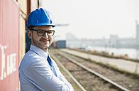 Portrait of businessman wearing blue hard hat - UUF000330