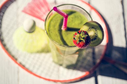 Glass of garnished kiwifruit smoothie, shuttlecocks and badmiton racket on wooden table - SARF000502