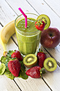 Glass of kiwifruit smoothie and fruits on wooden table - SARF000500