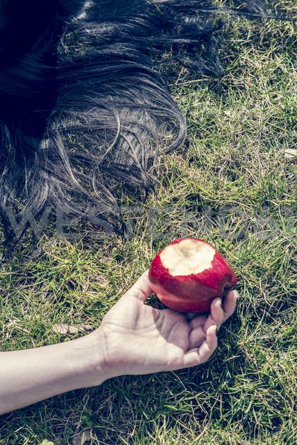 Hand of woman lying on grass holding bitten red apple - SARF000516 - Sandra Rösch/Westend61