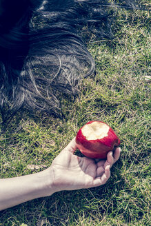 Hand of woman lying on grass holding bitten red apple - SARF000516
