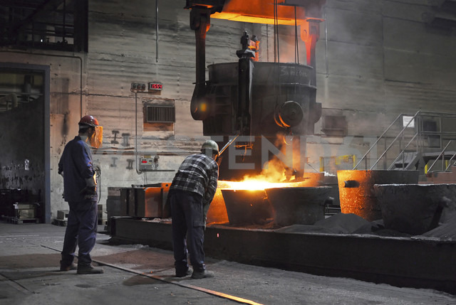 Two workers at melting pot in a foundry - SCH000156