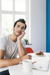 Portrait of pondering young man sitting at breakfast table with newspaper - MFF001005