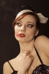 Portrait of young woman with lipstick on cheek clothed in 20ies style - FBF000373