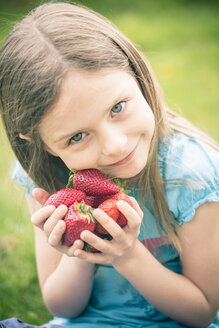 Portrait of smiling little girl holding handful of strawberries - SARF000519