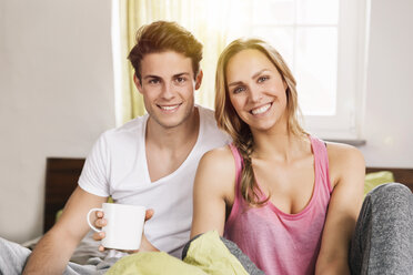 Young couple with cup of coffee sitting on their bed - MFF001034