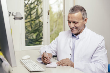 Smiling doctor sitting at desk with computer - MFF001068