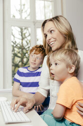 Happy mother with two sons looking at computer screen - MFF001059