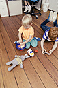 Two brothers playing on floor of a workroom - MFF001056
