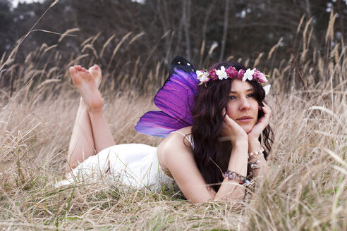 Germany, Young woman with wings lying on meadow - AFF000056