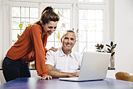 Mature man and young woman with laptop at home - MFF001053
