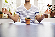 Young man meditating over a small pot of a succulent - MFF001041